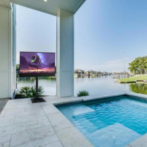 Seura outdoor television with floor stand on a luxury stone patio with a sunken pool overlooking a marina